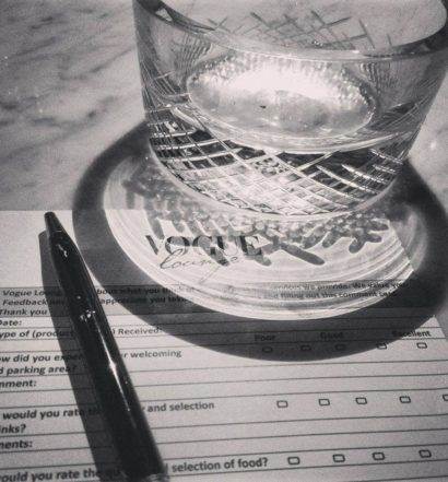 glass on top of a comment card in black and white